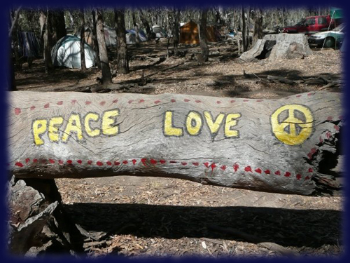 Tree log with Peace symbol and text and love painted on.